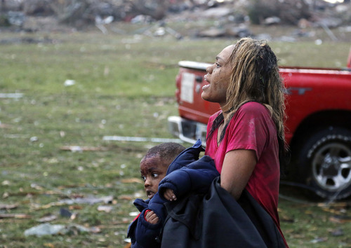 A woman carries an injured child to a triage center near the Plaza Towers Elementary School in Moore, Okla., Monday, May 20, 2013. A tornado as much as a mile (1.6 kilometers) wide with winds up to 200 mph (320 kph) roared through the Oklahoma City suburbs Monday, flattening entire neighborhoods, setting buildings on fire and landing a direct blow on an elementary school. (AP Photo Sue Ogrocki)
