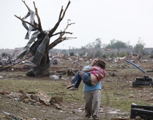 A woman carries her child through a field near the collapsed Plaza Towers Elementary School in Moore, Okla., Monday, May 20, 2013. (AP Photo Sue Ogrocki)