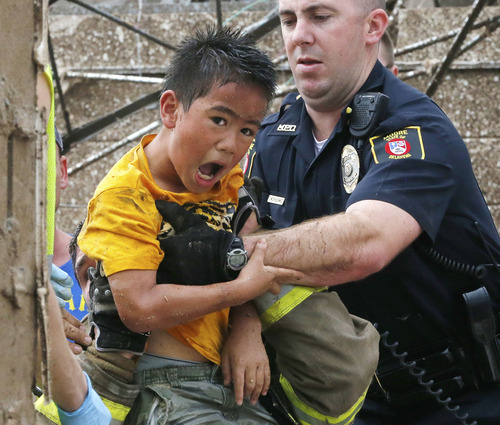 A boy is pulled from beneath a collapsed wall at the Plaza Towers Elementary School following a tornado in Moore, Okla., Monday, May 20, 2013. (AP Photo Sue Ogrocki)
