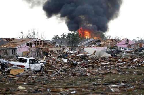 A fire burns in the Tower Plaza Addition in Moore, Okla., following a tornado Monday, May 20, 2013. A tornado as much as a mile (1.6 kilometers) wide with winds up to 200 mph (320 kph) roared through the Oklahoma City suburbs Monday, flattening entire neighborhoods, setting buildings on fire and landing a direct blow on an elementary school. (AP Photo Sue Ogrocki)