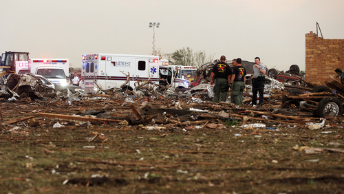 Ambulances are parked at Plaza Towers Elementary School as workers continue to dig through the rubble after a tornado moved through Moore, Okla., Monday, May 20, 2013. (AP Photo/Sue Ogrocki)