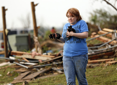 Rachel Hilton holds stray kittens she found in the debris of her parents' home at SW 149th and Stone Meadows Dr. after a tornado struck south Oklahoma City and Moore, Okla., Monday, May 20, 2013. (AP Photo/The Oklahoman, Nate Billings)