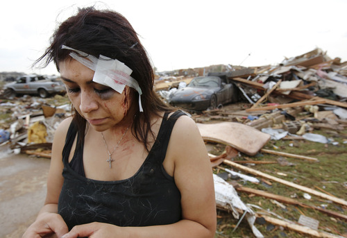 Cindy Wilson texts to friends after her home was destroyed in the afternoon tornado. Cindy and her husband, Staff Sgt. B. Wilson, took cover in their home's bathtub when the tornado hit. Cindy received a deep gash to her forehead and her wound  was treated by first responders at the scene. Tornado caused extensive damage in the Madison Place Addition, near SE 8 and Tower in Moore, on Monday, May 20, 2013.    (AP Photo/ The Oklahoman, Jim Beckel)