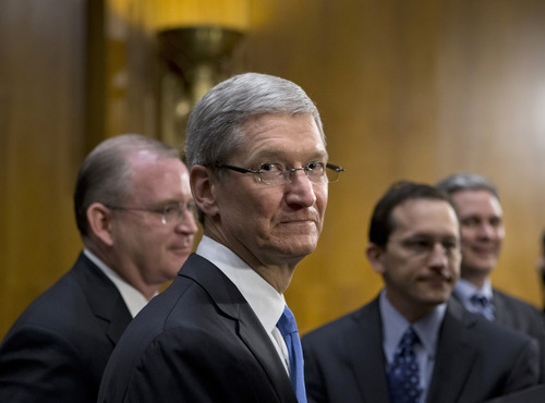 Apple CEO Tim Cook, center, is surrounded by his team during a break from testifying on Capitol Hill in Washington, Tuesday, May 21, 2013, before the Senate Homeland Security and Governmental Affairs Permanent subcommittee on Investigations as lawmakers examine the methods employed by multinational corporations to shift profits offshore and how such activities are affected by the Internal Revenue Code. Apple, the world's most valuable company, based in Cupertino, Calif., holds a billion dollars in an Irish subsidiary as a tax strategy, according to a report issued this week by the subcommittee.   (AP Photo/J. Scott Applewhite)