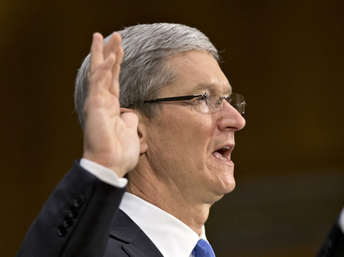Apple CEO Tim Cook is sworn in on Capitol Hill in Washington, Tuesday, May 21, 2013, prior to testifying before the Senate Homeland Security and Governmental Affairs Permanent subcommittee on Investigations hearing to examine the methods employed by multinational corporations to shift profits offshore and how such activities are affected by the Internal Revenue Code. Lawmakers want to hear from Cook how Apple, the world's most valuable company, based in Cupertino, Calif., holds a billion dollars in an Irish subsidiary as a tax strategy, according to a report issued this week by the subcommittee.  (AP Photo/J. Scott Applewhite)