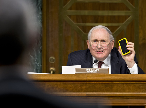 Senate Homeland Security and Governmental Affairs Permanent subcommittee on Investigations Chairman Sen. Carl Levin, D-Mich., holds up his own Apple iPhone, on Capitol Hill in Washington, Tuesday, May 21, 2013, as he presses Apple CEO Tim Cook for answers about how Apple, the world's most valuable company, and based in Cupertino, Calif., diverts a billion dollars to an Irish subsidiary as a tax strategy, according to a report issued this week by the subcommittee.  (AP Photo/J. Scott Applewhite)