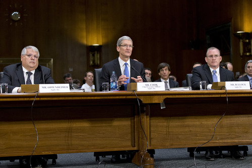 Apple CEO Tim Cook, center, flanked by Apple chief financial officer Peter Oppenheimer, left, and Phillip A. Bullock, Apple's head of Tax Operations, testifies on Capitol Hill in Washington, Tuesday, May 21, 2013, before the Senate Homeland Security and Governmental Affairs Permanent subcommittee on Investigations hearing to examine the methods employed by multinational corporations to shift profits offshore and how such activities are affected by the Internal Revenue Code. Apple, the world's most valuable company, based in Cupertino, Calif., holds a billion dollars in an Irish subsidiary as a tax strategy, according to a report issued this week by the subcommittee.  (AP Photo/J. Scott Applewhite)
