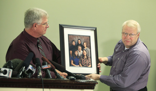 Chuck Cox, right, the father of Susan Powell, who was reported missing Dec. 7, 2009, in Utah, is helped by family friend Michael Gifford, left, as he talks to reporters about a photo of his family, with Susan Cox shown at upper right, Thursday, Dec. 17, 2009, in Puyallup, Wash. Powell's family said Thursday they are saddened but not surprised that her husband Josh Powell has been named a person of interest in the investigation. (AP Photo/Ted S. Warren)