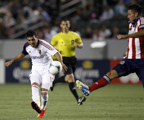 Real Salt Lake midfielder Javier Morales (11) lofts a shot over Chivas USA defender Steve Purdy Ramos, right, defending, during the second half of an MLS soccer game in Carson, Calif., Sunday, May 19, 2013. Real Salt Lake won the match 4-1.    (AP Photo/Alex Gallardo)