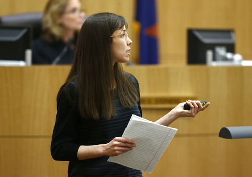 Jodi Arias shows her family photographs as she addresses the jury on Tuesday, May 21, 2013 during the penalty phase of her murder trial at Maricopa County Superior Court in Phoenix, AZ.  Jodi Arias was convicted of first-degree murder in the stabbing and shooting to death of Travis Alexander, 30, in his suburban Phoenix home in June 2008. (AP Photo/The Arizona Republic, Rob Schumacher, Pool)
