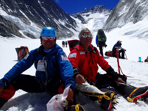 In this Friday, May 17, 2013 photo distributed by Miura Dolphins, 80-year-old Japanese adventurer Yuichiro Miura, right, and his son, Gota, rest on their way to a camp at 6,500 meters (21,325 feet) from a camp at 6,050 meters (19,849 feet) during their attempt to scale the summit of Mount Everest. According to his management office, Miura plans to reach the 8,850-meter (29,035-foot) peak on Thursday, May 23 to be the world's oldest person to reach the world's highest peak. (AP Photo/Miura Dolphins)  MANDATORY CREDIT