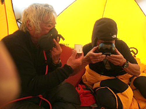 In this May 22, 2013 photo distributed by Miura Dolphins Co. Ltd., 80-year-old Japanese extreme skier Yuichiro Miura, left, uses oxygen mask and his son, Gota sips green tea as they take a rest in a tent at their South Col camp at 8,000 meters (26,247 feet) before their departure for Camp 5 during their attempt to scale the summit of Mount Everest. Miura, who climbed Mount Everest five years ago, but just missed becoming the oldest man to reach the summit, was back on the mountain Wednesday to make another attempt at the title. (AP Photo/Miura Dolphins Co. Ltd.)  MANDATORY CREDIT