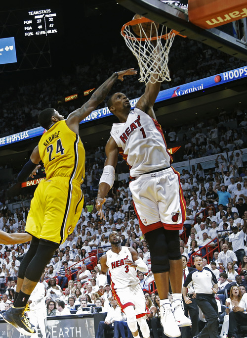 Miami Heat center Chris Bosh (1) scores against Indiana Pacers forward Paul George (24) defends during the second half of Game 1 in their NBA basketball Eastern Conference finals playoff series, Wednesday, May 22, 2013 in Miami. (AP Photo/Lynne Sladky)