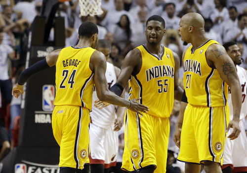Indiana Pacers forward Paul George (24) is congratulated on his basket by Roy Hibbert (55) and David West (21)  during the second half of Game 1 in their NBA basketball Eastern Conference finals playoff series against the Miami Heat, Wednesday, May 22, 2013 in Miami. (AP Photo/Lynne Sladky)