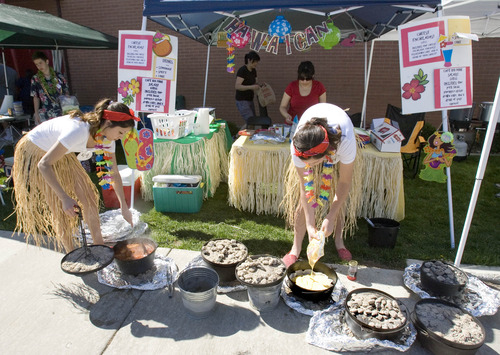 Paul Fraughton  |  The Salt Lake Tribune Mandy Stauffer and Allison Campbell dress in grass skirts as they prepare a Hawiian-themed Dutch oven entry in Riverview Jr. High School's ninth-grade Dutch oven cook-off.                           Friday, May 10, 2013