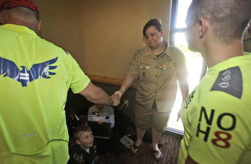 Former Boys Scout leader Jennifer Tyrrell, center, is greeted as her son and current Boy Scout Cruz Burns, 8, bottom, looks on during the Equal Scouting Summit being held near where the Boy Scouts of America are holding their annual meeting Wednesday, May 22, 2013, in Grapevine, Texas. Delegates to the Boys Scouts of America meeting are expected to address a proposal to allow gay scouts into the organization. (AP Photo/LM Otero)