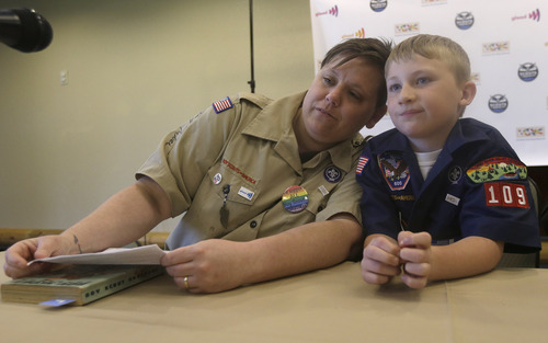 Former Boys Scout leader Jennifer Tyrrell, left, rests her head on her son and current Boy Scout Cruz Burns, 8, before an news conference at the Equal Scouting Summit being held near where the Boy Scouts of America are holding their annual meeting Wednesday, May 22, 2013, in Grapevine, Texas. Delegates to the Boys Scouts of America meeting are expected to address a proposal to allow gay scouts into the organization. (AP Photo/LM Otero)