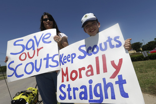 Terri Hall, left, of San Antonio, Texas, stands with her son Nathaniel Hall, 8, as they hold signs near where the Boy Scouts of America are holding their annual meeting Wednesday, May 22, 2013, in Grapevine, Texas. Delegates to the meeting are expected to address a proposal to allow gay scouts into the organization. (AP Photo/LM Otero)