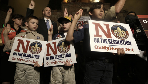 Boy Scouts from right, Joey Kalich, 10, Steven Grime, 7, and Jonathon Grime, 9, raise their hands at the close of a news conference held by people against the change in the Boy Scouts of America gay policy Wednesday, May 22, 2013, in Grapevine, Texas. Delegates to the Boys Scouts of America meeting nearby are expected to address a proposal on Thursday to allow gay scouts into the organization. (AP Photo/LM Otero)