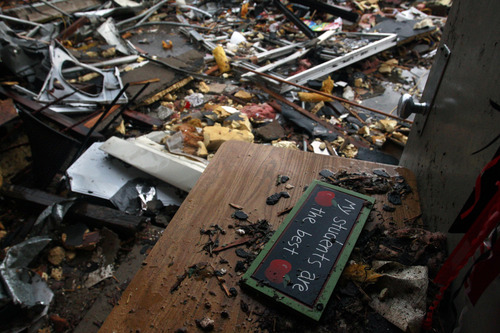A teacher's classroom sign sits on a desk propping open a door amid the wreckage of Plaza Towers Elementary School, where seven children were killed earlier in the week when a tornado hit Moore, Okla., Thursday, May 23, 2013. The huge tornado roared through the Oklahoma City suburb Monday, flattening entire neighborhoods and destroying the elementary school with a direct blow as children and teachers huddled against winds up to 200 mph. (AP Photo/Brennan Linsley)