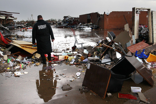 A deputy sheriff walks through the rubble at Plaza Towers Elementary School, where seven children were killed earlier in the week when a tornado hit Moore, Okla., Thursday, May 23, 2013. The huge tornado roared through the Oklahoma City suburb Monday, flattening entire neighborhoods and destroying the elementary school with a direct blow as children and teachers huddled against winds up to 200 mph. (AP Photo/Brennan Linsley)
