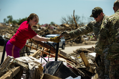 In this Wednesday, May 22, 2013 photo provided by the U.S. Air Force, U.S. Air Force Tech. Sgt. Ben Lake, Joint Terminal Attack Controller, 138th Combat Training Flight, passes a family photo to Elise Hopkins while searching through the debris looking for salvageable items in what is left of her home, in Moore, Okla. On Monday, a tornado leveled homes, crushed vehicles, and killed more than 20 people in the area. More than 115 Oklahoma National Guard personnel have been activated to assist in the rescue and relief efforts. (AP Photo/U.S. Air Force, Staff Sgt. Jonathan Snyder)