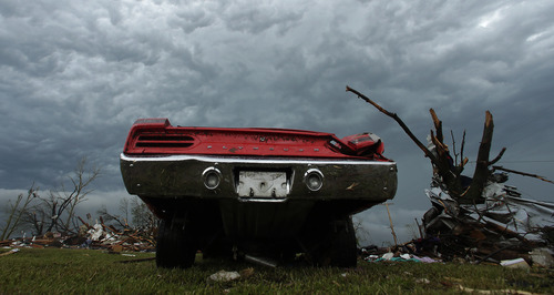 An old car sits wrecked tornado debris Thursday, May 23, 2013, in Moore, Okla. Cleanup continues three days after a huge tornado roared through the Oklahoma City suburb, flattening a wide swath of homes and businesses. (AP Photo/Charlie Riedel)