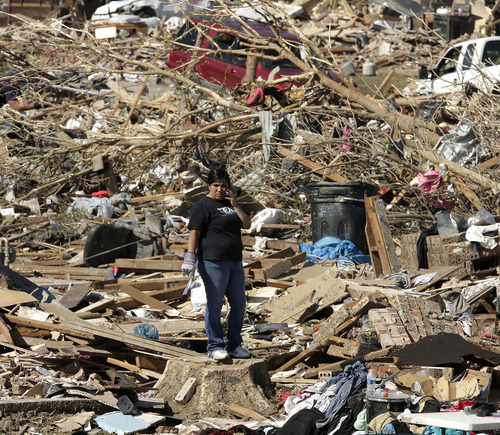An unidentified woman looks over the scene as residents sort through their tornado-ravaged homes Wednesday, May 22, 2013, in Moore, Okla. Cleanup continues two days after a huge tornado roared through the Oklahoma City suburb, flattening a wide swath of homes and businesses. (AP Photo/Charlie Riedel)