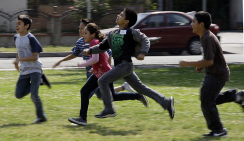 FILE - This May 10, 2011 file photo shows children at Tracy Elementary School running across a field as they take part in after-school exercise activities on the campus in Baldwin Park, Calif. Reading, writing, `rithmetic - and PE?  The prestigious Institute of Medicine is recommending that schools provide opportunities for at least 60 minutes of physical activity each day for students and treat physical education as a core subject. The report says only about half of the nation's youngsters are getting at least an hour of vigorous or moderate physical activity every day. (AP Photo/Reed Saxon, File)