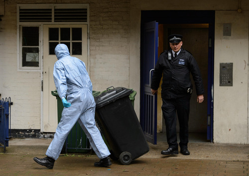 A Police forensics officer removes items from an apartment in Greenwich, south east London, where 22-year old Michael Adebowale, is registered as living, Friday May 24, 2013.  Searches continued Friday at various addresses in connection with two attackers who killed Drummer Lee Rigby in the Woolwich area of London on Wednesday. (AP Photo / Dominic Lipinski, PA) UNITED KINGDOM OUT - NO SALES - NO ARCHIVES