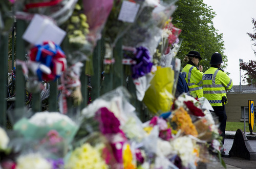 Police secure the area near flowers tributes placed outside the Woolwich Barracks, in London, Friday, May 24, 2013,  in response to the bloody attack on Wednesday when a British soldier was killed in the nearby street.  London's Metropolitan Police said more than 1,000 officers will be sent to potential trouble spots as Britain is bracing for any clashes with right-wing extremists and even possible copycat terror attacks after the brutal slaying of a young soldier.  (AP Photo/Bogdan Maran)