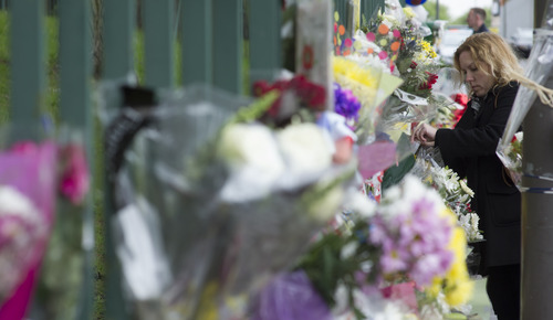 A women lays flowers outside the Woolwich Barracks, in London, Friday, May 24, 2013, in response to the bloody attack on Wednesday when a British soldier was killed in the street. London's Metropolitan Police said more than 1,000 officers will be sent to potential trouble spots as Britain is bracing for any clashes with right-wing extremists and even possible copycat terror attacks after the brutal slaying of a young soldier. (AP Photo/Bogdan Maran)
