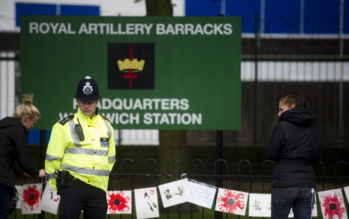 A police officer stands guard outside the Woolwich Barracks, in London, Friday, May 24, 2013, in response to the bloody attack on Wednesday when a British soldier was killed in the nearby street.  London's Metropolitan Police said more than 1,000 officers will be sent to potential trouble spots as Britain is bracing for any clashes with right-wing extremists and even possible copycat terror attacks after the brutal slaying of a young soldier.  (AP Photo/Bogdan Maran)