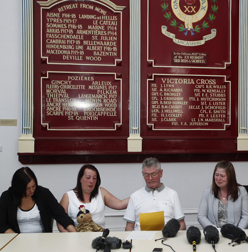 """Family members of murdered British soldier Lee Rigby, from left to right, sister Sara McClure, his mother Lyn, stepfather Ian, and his wife Rebecca Rigby, in front of a roll of honour board showing the deeds and sacrifices of the regiment, as his stepfather reads a statement during a press conference at the Regimental HQ of his unit, the Royal Regiment of Fusiliers at Bury in Greater Manchester, England, Friday May 24, 2013. Ian Rigby thanked people for their support and including the tribute """"You fought bravely and with honour died"""".  Drummer Lee Rigby had served in Afghanistan and was attached to the Regimental Recruiting Team when he was hacked to death in broad daylight on Wednesday afternoon in Woolwich, south-east London. Two suspects were shot and arrested at the scene and remain in police custody. (AP Photo/Dave Thompson)"""