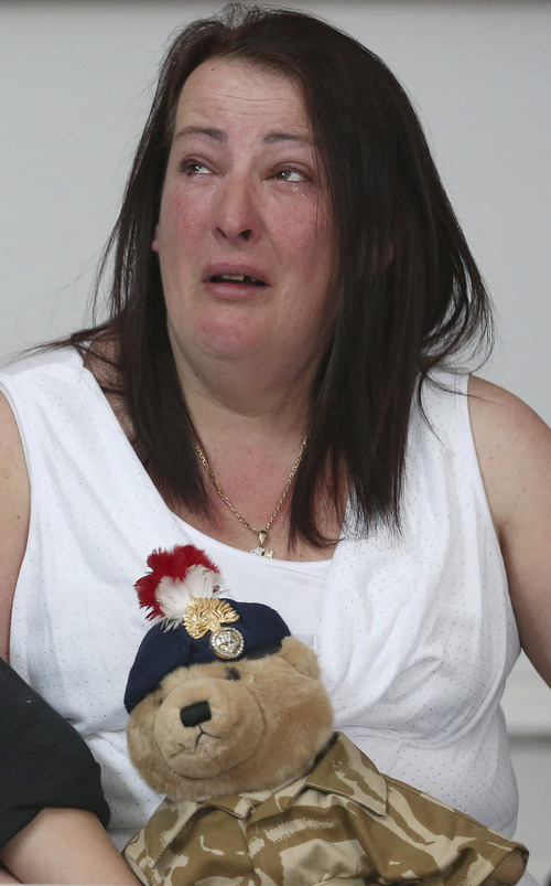 """Lyn Rigby, the mother of murdered soldier Lee Rigby, holds a teddy bear bought by Lee for his son, Jack, reacts as his stepfather Ian Rigby, not pictured, reads a statement during a press conference at the Regimental HQ of his unit, the Royal Regiment of Fusiliers at Bury in Greater Manchester, England, Friday May 24, 2013.  Ian Rigby thanked people for their support and including the tribute """"You fought bravely and with honour died"""".  Drummer Lee Rigby had served in Afghanistan and was attached to the Regimental Recruiting Team when he was hacked to death in broad daylight on Wednesday afternoon in Woolwich, south-east London. Two suspects were shot and arrested at the scene and remain in police custody. (AP Photo/Dave Thompson)"""