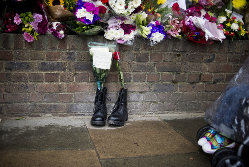 Military boots are laid in tribute outside the Woolwich Barracks, in London, Friday, May 24, 2013, in response to the bloody attack on Wednesday when a British soldier was killed in the nearby street.  London's Metropolitan Police said more than 1,000 officers will be sent to potential trouble spots as Britain is bracing for any clashes with right-wing extremists and even possible copycat terror attacks after the brutal slaying of a young soldier.  (AP Photo/Bogdan Maran)