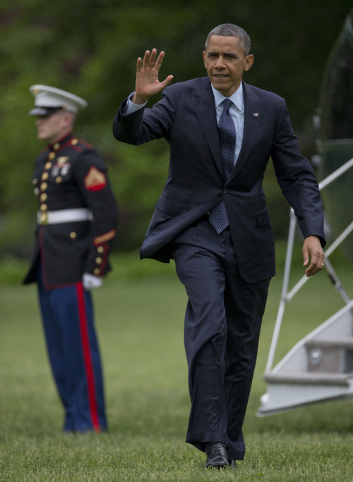 President Barack Obama waves as he steps off of Marine One as he arrives on the South Lawn of the White House, Friday, May 24, 2013, in Washington, as he returns from Annapolis where he delivered the commencement address at the United States Naval Academy. (AP Photo/Carolyn Kaster)