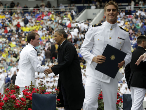 President Barack Obama congratulates a graduate as another one celebrates at the United States Naval Academy graduation ceremony in Annapolis, Md., Friday, May 24, 2013. (AP Photo/Pablo Martinez Monsivais)