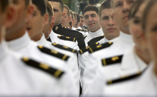 A member of the 2013 graduating class of the United States Naval Academy peeks over the shoulder of a fellow graduates to listen to President Barack Obama during the commencement ceremony at the Academy in Annapolis, Md., Friday, May 24, 2013. The president urged new graduates to exhibit honor and courage in tackling incidents of sexual assault as they assume leadership positions in the military. (AP Photo/Pablo Martinez Monsivais)
