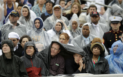 Guests sit in the stands in the rain during the commencement ceremonyfor the United States Naval Academy in Annapolis, Md., Friday, May 24, 2013. President Barack Obama urged new graduates to exhibit honor and courage in tackling incidents of sexual assault as they assume leadership positions in the military. (AP Photo/Pablo Martinez Monsivais)