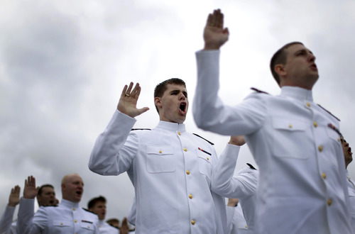 Graduating U.S. Naval Academy Midshipmen take the U.S. Navy oath of office during the Academy's graduation and commissioning ceremonies, Friday, May 24, 2013, in Annapolis, Md. President Barack Obama urged new graduates to exhibit honor and courage in tackling incidents of sexual assault as they assume leadership positions in the military. (AP Photo/Patrick Semansky)