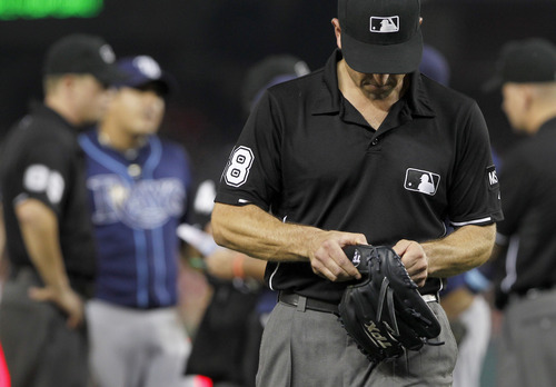 FILE - In this June 9, 2012 file photo, umpire Chris Guccione leaves with the glove of Tampa Bay Rays relief pitcher Joel Peralta after Peralta was ejected in the eighth inning for having a foreign substance on his glove during a baseball game against the Washington Nationals in Washington. Ex-minor leaguer turned law school grad Garrett Broshuis says there is cheating in baseball, all the time. (AP Photo/Alex Brandon, File)