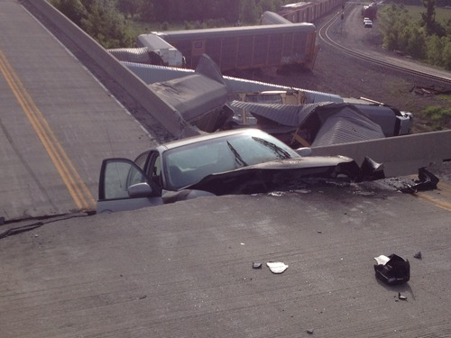 A car lies in-between damaged sections of a highway overpass near Rockview, Mo. on Saturday, May 25, 2013. Authorities said the roadway collapsed when rail cars slammed into one of the bridge's pillars after a cargo train collision. Seven people were injured, though none seriously. (AP Photo/KFVS, Michael Mohundro)