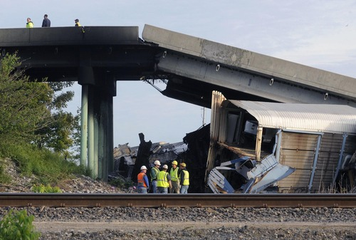 Emergency personnel investigate the Route M overpass at Rockview, Mo., about 10 miles south of Cape Girardeau, Mo., after it collapsed onto the railroad tracks, Saturday, May 25, 2013. The National Transportation Safety Board has launched an investigation into the cause of a cargo train collision that partially collapsed a highway overpass in southeast Missouri, injuring seven people.  (AP Photo/Southeast Missourian, Fred Lynch)