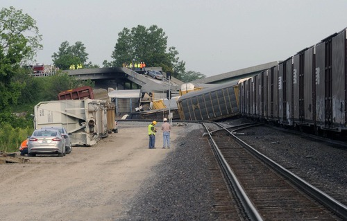 Officials survey the scene just east of the Route M overpass where several train cars derailed on the Burlington Northern Santa Fe train near Rockview, Mo. Saturday, May 25, 2013. The National Transportation Safety Board has launched an investigation into the cause of a cargo train collision that partially collapsed a highway overpass in southeast Missouri, injuring seven people.  (AP Photo/Southeast Missourian, Fred Lynch)