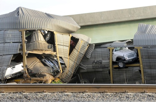 New vehicles being transported on a Burlington Northern Santa Fe train poke out of their damaged rail car after a Union Pacific train collided with it at Rockview, Mo. Saturday, May 25, 2013. The National Transportation Safety Board has launched an investigation into the cause of a cargo train collision that partially collapsed a highway overpass in southeast Missouri, injuring seven people.  (AP Photo/The Southeast Missourian, Fred Lynch)
