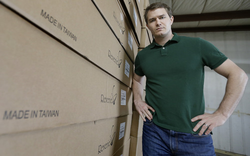 In this Friday, May 17, 2013, photo, Martin Rawls-Meehan, CEO of Reverie, poses at the company warehouse, next to product made in Taiwan. The company is working to expand manufacturing in the United States. (AP Photo/David Duprey)