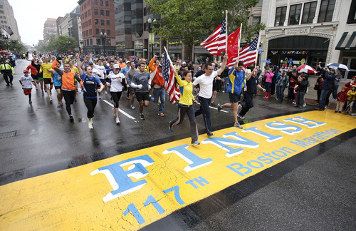 Runners who were unable to finish the Boston Marathon on April 15 because of the bombings cross the finish line on Boylston Street after the city allowed them to finish the last mile of the race in Boston, Saturday, May 25, 2013. (AP Photo/Winslow Townson)
