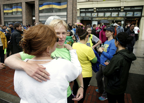 Nick Pelton, of Florida, hugs his mom, Colleen, after watching runners who were unable to finish the Boston Marathon because of the bombings on April 15, cross the finish line on Boylston Street after the city allowed them to finish the last mile of the race, in Boston, Saturday, May 25, 2013. (AP Photo/Winslow Townson)