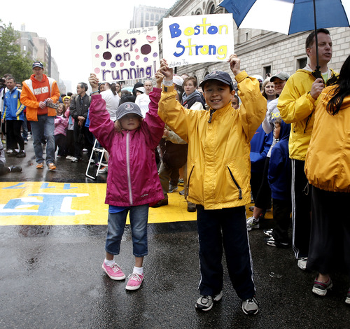 Maxwell Surprenant, right, and Emily Perron hold up signs cheering on runners who were unable to finish the Boston Marathon on April 15 because of the bombings after the city allowed them to finish the last mile of the race in Boston, Saturday, May 25, 2013. (AP Photo/Winslow Townson)
